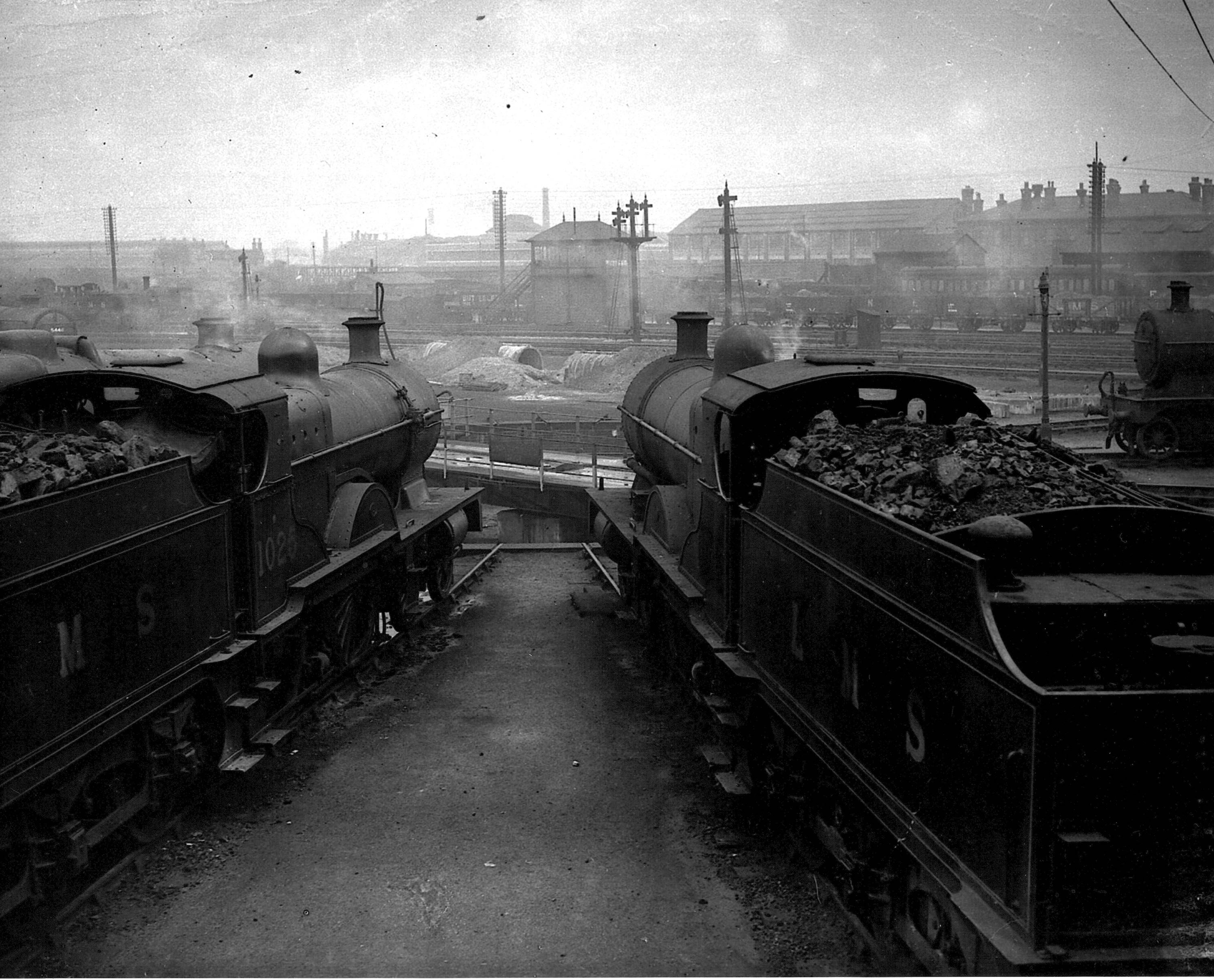 A photograph taken with two locomotives in the foreground stabled around a turntable at Derby's 'Four Shed'. We are looking over to Way & Works signal box with air raid shelters being contructed in the middle-distance. The LMS research laboratories on London Road are visible in the background.