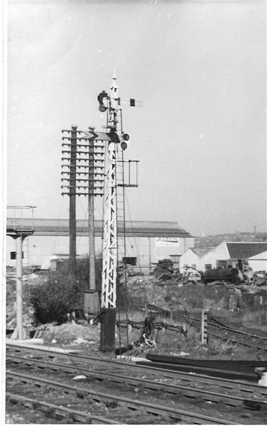 A wooden latice post signal carrying a home and distant signal arm on opposite side of the post, viewd from a passing train across the goods lines with Derby Corporation Sidings in the background