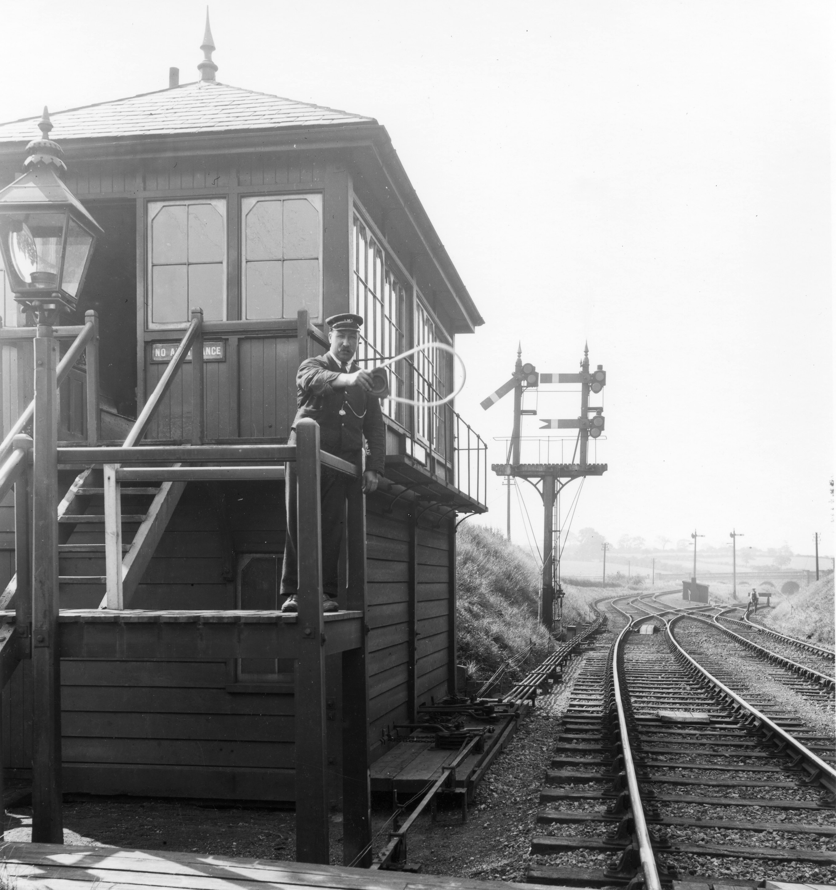 A LMS signalman posing on the steps of his signal box holdong out a single line toekn for a (non-existent) train to collect.